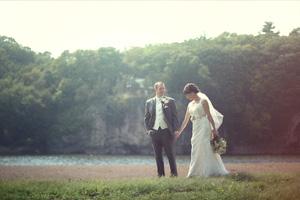 Bride and groom walking along Cedar River near Iowa City