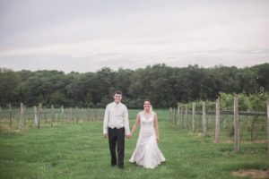 bride and groom walking holding hands in winery